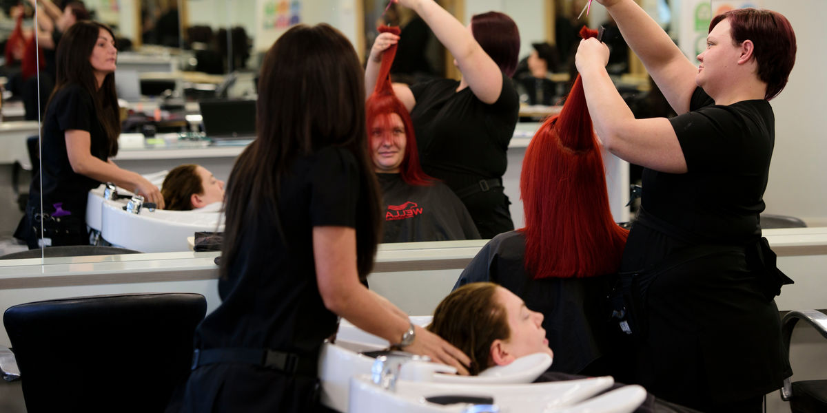 Hairdressing Students Cutting Hair In Salon