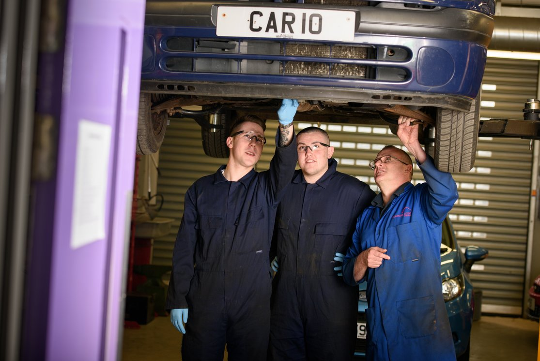 Automotive inspecting underneath car with lecturer %283%29 gallery